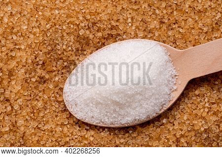 Wooden Spoon Full Of Refined Granulated Sugar On Top Of Brown Granulated Sugar.