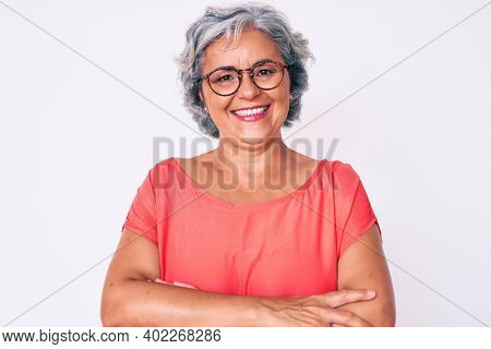 Senior hispanic grey- haired woman wearing casual clothes and glasses happy face smiling with crossed arms looking at the camera. positive person.