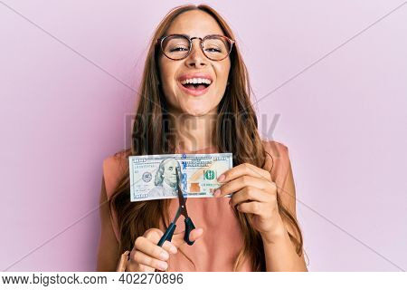 Young brunette woman cutting dollars with scissors for currency devaluation smiling and laughing hard out loud because funny crazy joke.