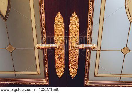 Door Handles With An Old Double Door. Golden Handle Door Entrance. Luxury Gold Handle. Classical Sty