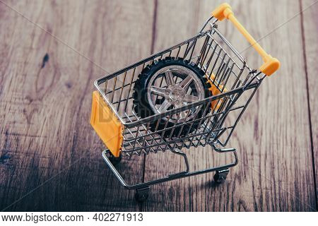 Shopping Trolley On Wooden Table, Tyre In The Trolley