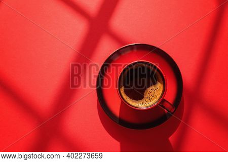 Cup of coffee on red background at direct sunlight. Red cup of coffee with shadows on red background.