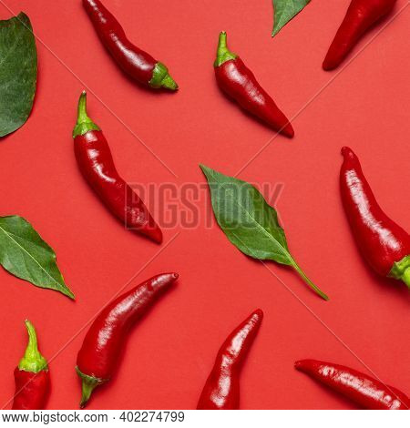 Chili Peppers Background. Hot Red And Green Fresh Chili Peppers On Red Background Flat Lay Top View.