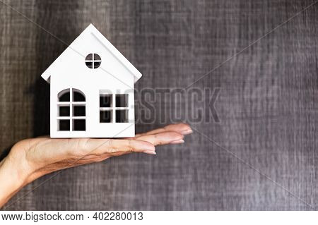 Hand Holding A House Model. Real Estate Agent Offer House, Property Insurance And Security. Buy And