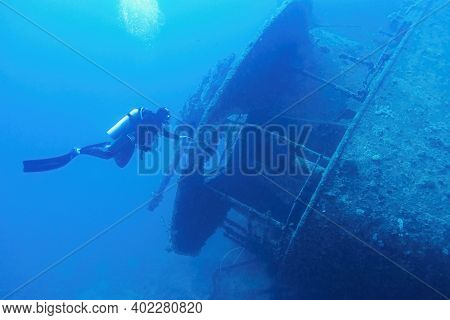 Man Scuba Diver Swimming Near The Ship Wreck In Blue Deep Water. Ship Wreck Ss Thistlegormm, Red Sea