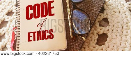 Code Of Ethics Words On Notebook, Pen, Glasses, Crochet Cloth. Business Concept. Moral Rules Ethical