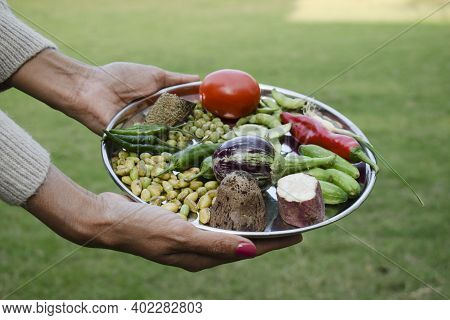 Woman Holding Plate Of Vegetables Used For Making Undhiyu Or Oondhiyu For Preparation During Uttaray