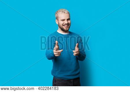 Caucasian Man With Blonde Hair And Beard Is Pointing At Camera Blinking And Smile On A Blue Studio W
