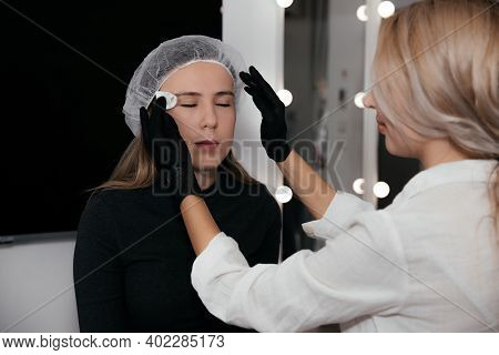 Permanent Makeup Artist In Black Gloves Prepares The Client's Face With The Procedure, Cleans The Ey