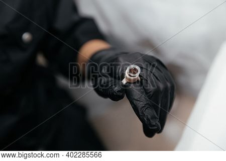 Finger In A Black Glove Is Wearing An Permanent Paint Ring With Brown Pigment. Close-up Of Pigment C