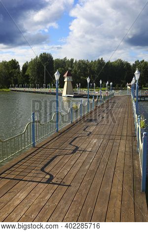 A Footbridge Over The Water Across The Lake