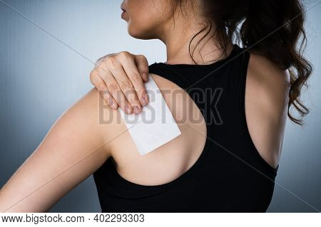 Woman Applying Stiff Shoulder Pain Patch After Injury
