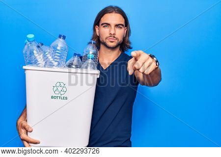 Young handsome man holding recycling wastebasket with plastic bottles pointing with finger to the camera and to you, confident gesture looking serious