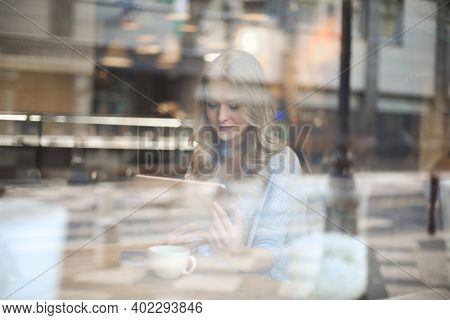 young woman writes with a tablet in a cafe