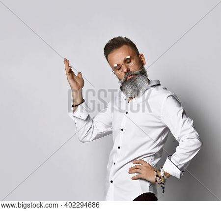 Confused Stylish Bearded Hipster Man With Glasses Raising His Hand Sharing Thoughts, Looking Up. A H