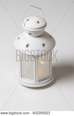 White Christmas Lantern Wearing Stars. The Lantern Shines And Stands On A White Table.
