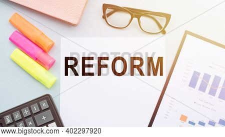 Reform A Word On Your Desktop With A Calculator, Markers, Glasses And Financial Charts.
