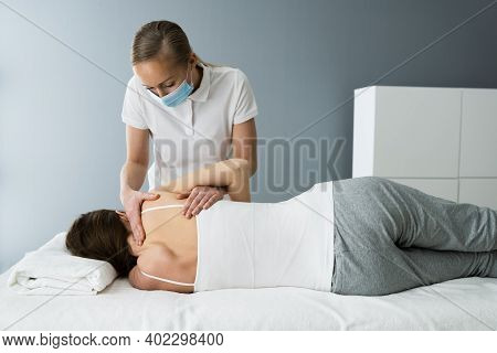 Rehab Shoulder Treatment By Sports Masseur And Physiotherapist In Face Mask