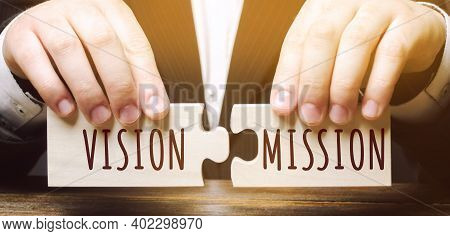 Businessman Connects Wooden Puzzles With The Words Vision Mission. Concept For Business Ideas And Go