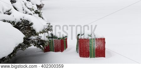 Two Large Red Chrstmas Decoration Gifts Outside Covered In Snow After A Storm Next To A Bush