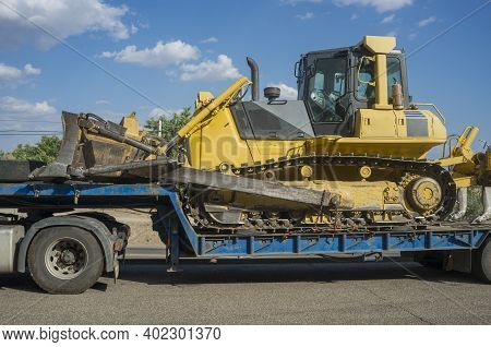Heavy-duty Truck Carrying Bulldozer Equipped With Multishank Ripper. Heavy Duty Transports