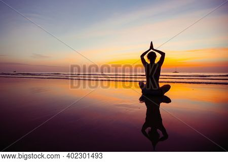 Yoga woman silhouette, practicing on the ocean side of awesome sunset.