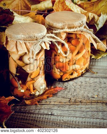 Autumn Concept. Preserved Food In Glass Jars On A Wooden Board. Marinated Mushrooms