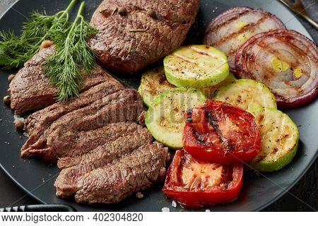 Roasted meat. Grilled beef steak and vegetables with spices on gray plate.  Steak menu. Grilled menu.