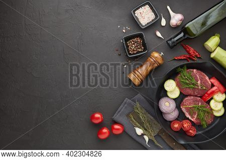 Raw fresh meat and vegetables. Beef steaks and cutting vegetables on grill  pan, olive oil and spices on black slate background. Top view with copy space. Steak menu