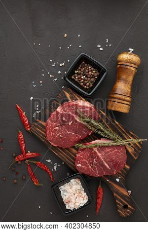 Raw fresh meat. Beef steaks on cutting board and spices on black slate background. Top view. Steak menu