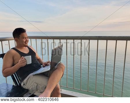 Happy Successful Asian Man Using Laptop While Sitting On His Balcony With Calm Blue Ocean Behind, Re