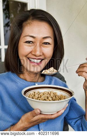 Photo of middle aged woman Eating Breakfast Cereal