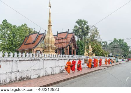 Luang Prabang, Laos : March-01-2019 : Buddhist Monks In A Rows With Alms Bowl Walking On The Street