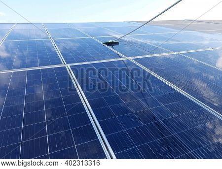 Cleaning Solar Modules With Wiper And Water, Sky Reflection On Solar Panels, Modules, Array.