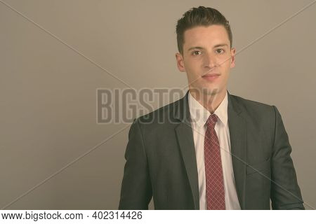 Young Handsome Businessman Wearing Suit Against Gray Background