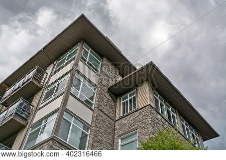 Top Of Residential Building With Stone Texture Wall On Cloudy Sky Background.