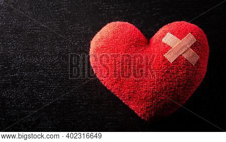 Close-up Of Cushioned Plaster Strip On Hand Made Red Heart With Dark Background. Broken Heart, Love,