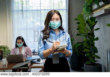 Asian Business People Wearing Protective Mask To Protect Against Covid-19 Working In Office With New