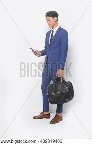 full body young businessman  wearing blue suit ,tie with white shirt and blue pants ,holding black handbag ,using cellphone with brown leather shoes
