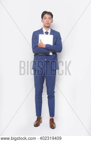 full body young businessman  wearing blue suit ,tie with white shirt and blue pants holding laptop with brown leather shoes
