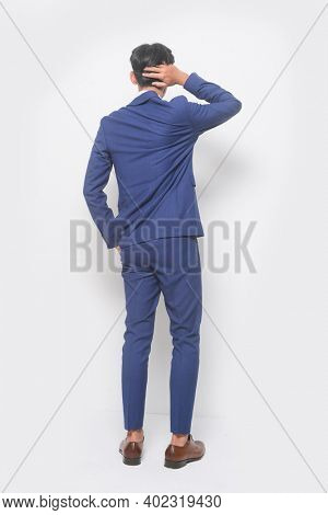 Back view full body young businessman  wearing blue suit ,tie with white shirt and blue pants with brown leather shoes
