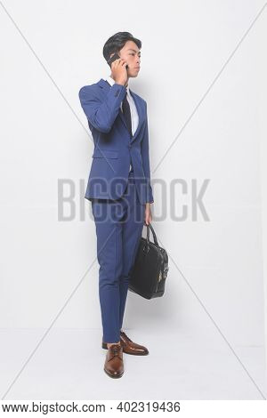 full body young businessman  wearing blue suit ,tie with white shirt and blue pants ,holding black handbag with cellphone with brown leather shoes