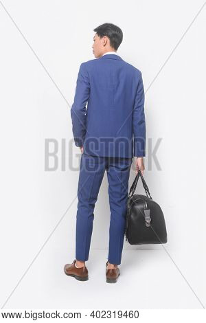 Back view -full body young businessman  wearing blue suit ,tie with white shirt and blue pants holding black handbag with brown leather shoes