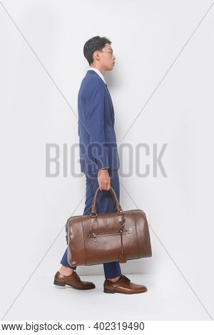 full body young businessman  wearing blue suit ,tie with white shirt and blue pants holding black handbag with brown leather shoes