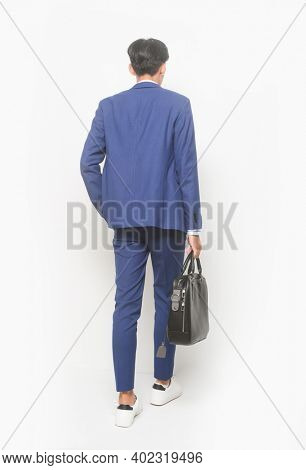 Back view full body young businessman  wearing blue suit ,tie with white shirt and blue pants holding black handbag with sneakers shoes