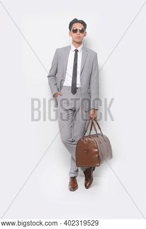 full body young businessman  wearing sunglasses , gray suit ,tie with white shirt and gray pants holding brown handbag with brown leather shoes