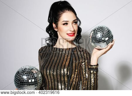 Sexy disco party woman with lond brunette hair. Sequin party dress, disco balls, bright makeup. Party time.