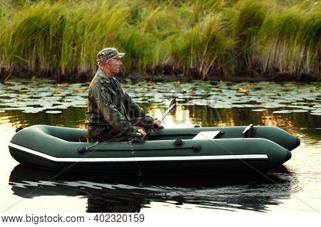An Elderly Man Is Sailing On A Rubber Boat With Oars On A Calm River. The Inspector Checks The Reser