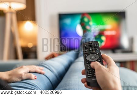 Woman Watching Tv At Home. Close Up Of Female Feet In Front Of Tv. Relaxing At Home With Tv. Leisure