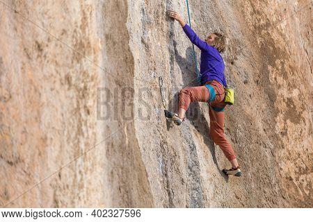 Girl Climbs A Rock-climbing Route. Outdoor Sports.